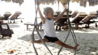 Cute baby girl playing and doing gymnastic exercise on the swing at sandy beach video