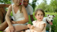 CLOSE UP: Cute baby girl playing with straw surrounded by loving parents and dog video