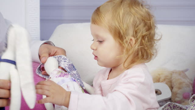 Cute baby girl plays with many toys at home video
