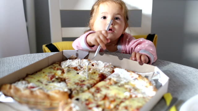 Cute baby girl seeing pizza for the fist time and feeding her mother video