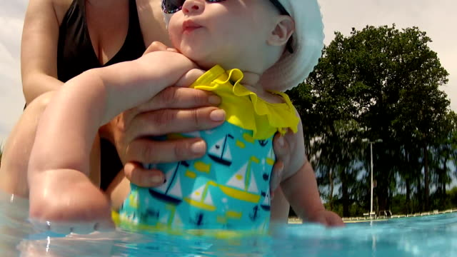 Cute baby having fun with mom at the pool video