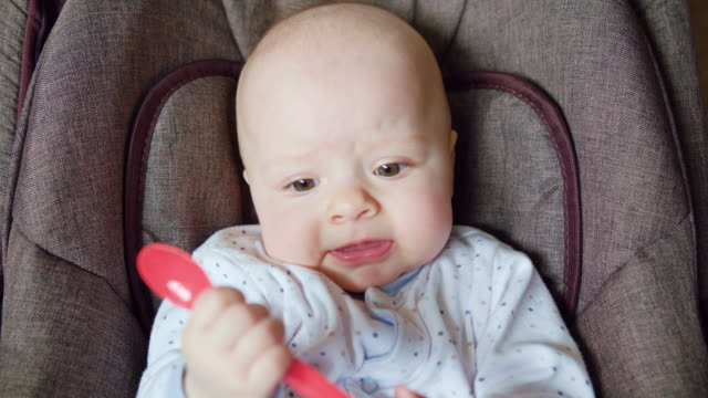 Cute Baby Lying in Pram Eating a Red Spoon video