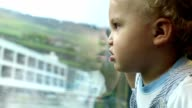 Cute baby traveling by train. Close up of baby on moving train. Toddler looking out train window, landscape passing by outside video