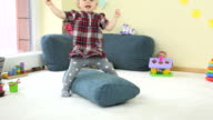 Cute blond toddler girl ride big pillow on floor and fall down at home. video