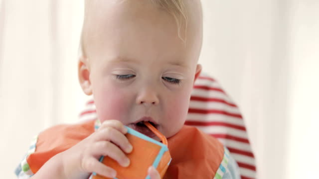 Cute boy drinking juice or milk from a packet video
