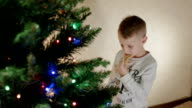 Cute boy eat gingerbread man near new year tree and hanging it back to the tree video