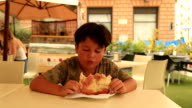 Cute boy eating pizza at the restaurant video
