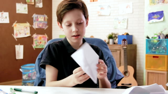 Cute boy folding origami airplane in his room video