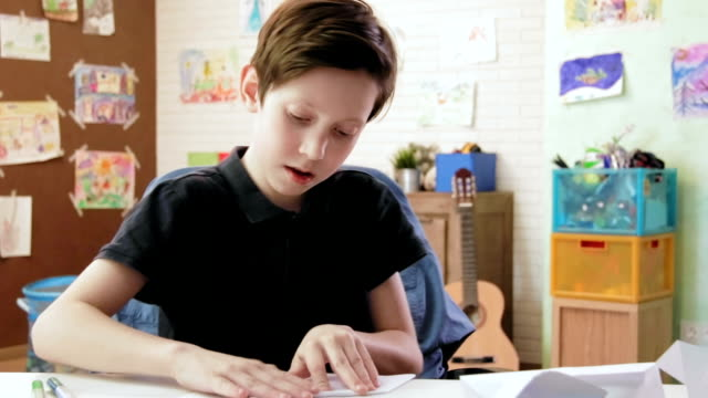 Cute boy folding origami in his room video