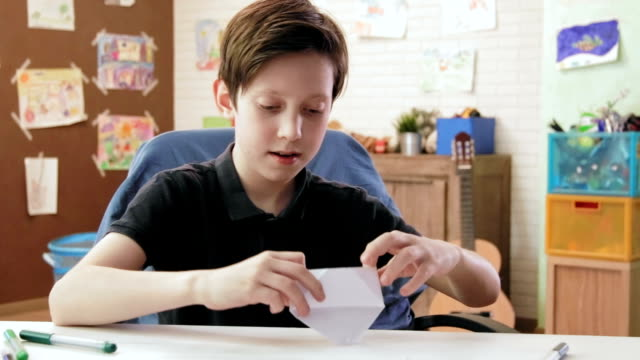 Cute boy folds origami boat and plays with it video