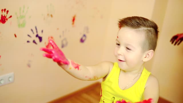Cute boy showing his hands in paint. Happy little child making colorful handsprint on the wall with mother together. video