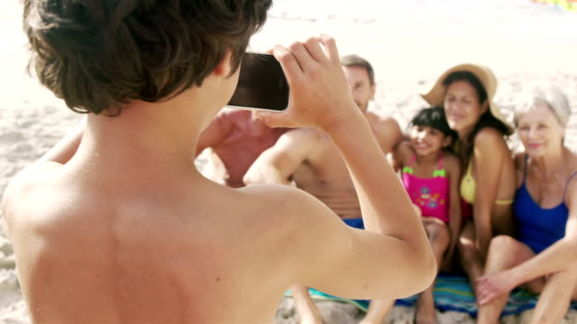 Cute boy taking picture of his family with smartphone video