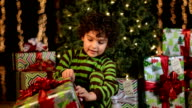 Cute Child Apprehensively Opens Christmas Present video
