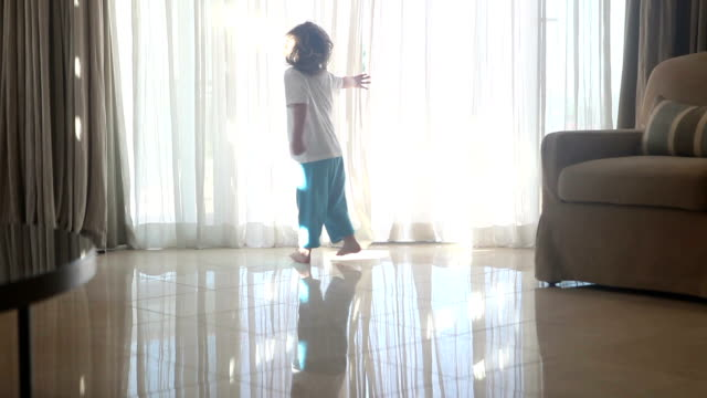 Cute child enthusiastically opening curtains in the morning video