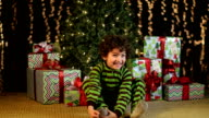Cute Child Excitedly Sits in Front of Christmas Tree video