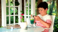 Cute child using smartphone at the summer cafe video