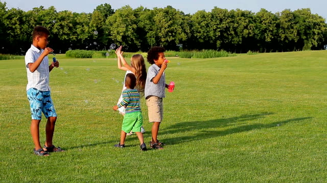 Cute children are playing on the evening glade. video