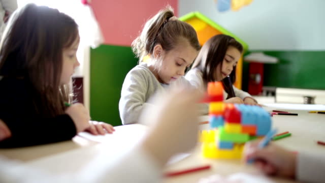 Cute children playing and writing in the classroom video