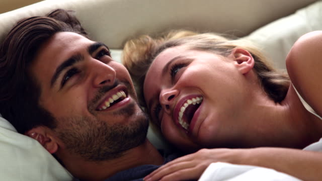 Cute couple laughing in bed video