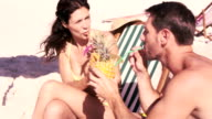 Cute couple on holidays drinking cocktails video