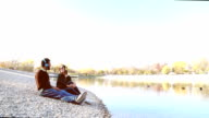 Cute couple sitting by lake and listening to music with headphones video