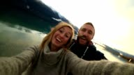 Cute couple take selfie by the lake at sunset video