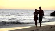 Cute couples stroll along beach video