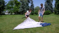 Cute curly girl and young guy pitches tent in park video