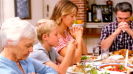 Cute family praying before eating dinner video