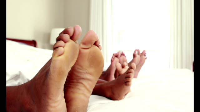 Cute family wiggling toes in bed video