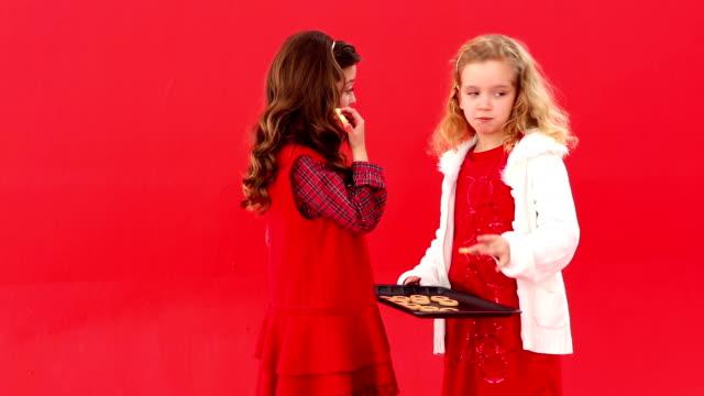 Cute festive sisters eating christmas cookies video