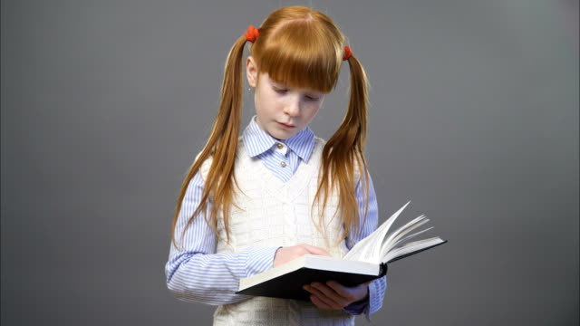 Cute ginger girl an a blue shirt and white vest is reading the book against gray background video