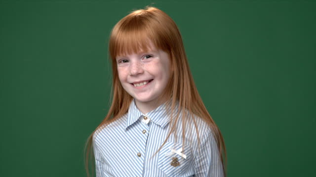 Cute ginger girl with freckles in a blue shirt smiling against chroma key green screen background video