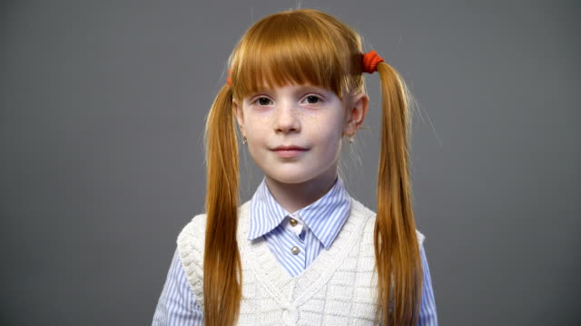 Cute ginger girl with two pigtails smiling against gray background video
