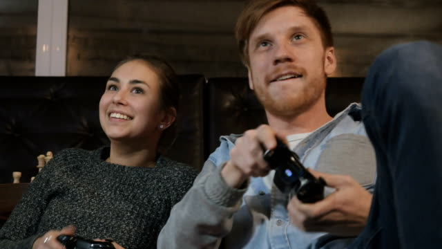 Cute girl and handsome guy playing on playstation video