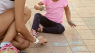 Cute girl and her mother drawing with chalk on sidewalk video