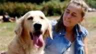 Cute girl brushing or grooming her golden retriever dog outdoors video