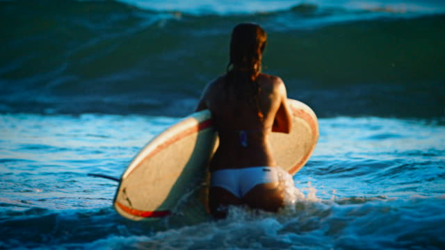 A cute girl carries her surfboard out in the the ocean to catch more waves in the summer sunset in San Diego, California. video