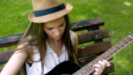 Cute girl learning how to play guitar in the park video