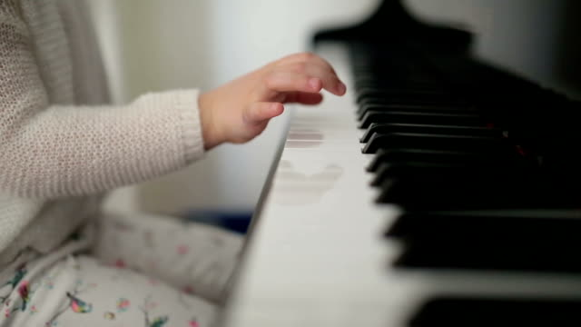 Cute girl learning to play piano video