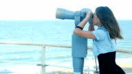 Cute girl looking at the sea through coin operated spy glass or public binoculars video