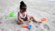 Cute girl playing sand on the beach video