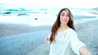 Cute girl pulling her boyfriend asking for walk near sea video