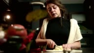 Cute girl slicing cutting onion with her eyes tearing crying video