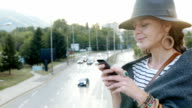 Cute girl standing on a bridge and texting on her smart phone video