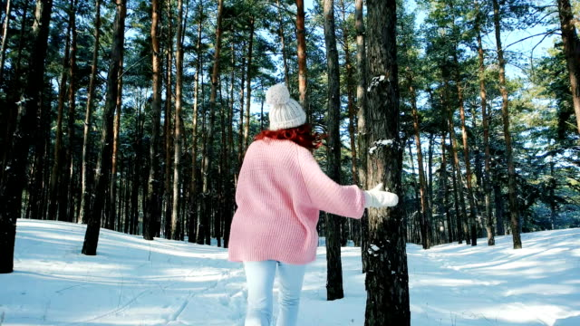 Cute girl walking in winter forest, a woman with red hair, running around in the snow video