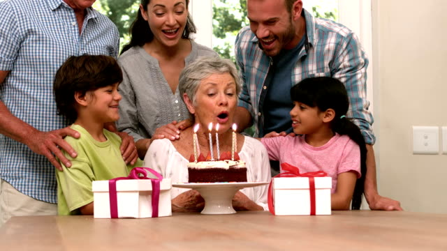 Cute grandmother blowing her candles with her family video
