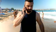 Cute guy walking on the beach and talking on the phone video