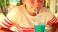 Cute happy child drinking a summer drink in a cafe video
