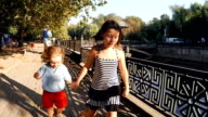 SLOW MOTION. Cute kids brother and sister walking by the river in the city park video